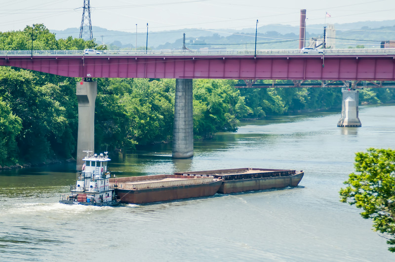 barge ship moving on water towards bridge