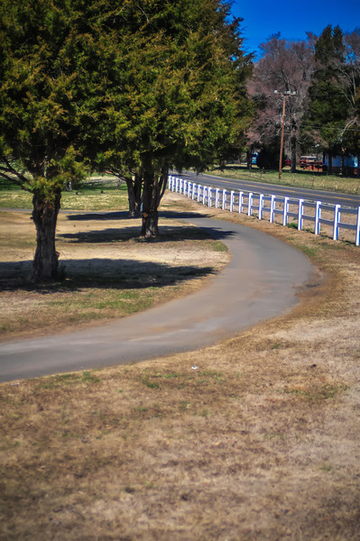 country sidewalk with white fence