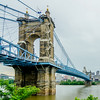 Cincinnati skyline and historic John A. Roebling suspension bridge cross Ohio River.
