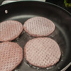 four hamburgers on frying pan