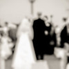 abstract of bride and groom standing before priest at end of isle
