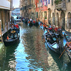 Gondolier's take a break from the hot Venetian sun on this shady canal in Venice Italy.