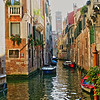 One of many fascinating, colorful canals in Venice Italy. The leaning tower in the background is Campaniles di Venezia or the Tower of Venice, yes it is really leaning. Many towers throughout Italy, especially in Venice, are leaning due to subsidence to some extent, none as prominant as Pisa of course.