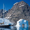 """Morgan's Cloud"", a McCurdy and Rhodes 56' cutter, seen beside an arch berg with glacier and mountain behind, a typical East Greenland scene.  The icecap reaches down to the sea in numerous glaciers and there are a floating profusion of bergs and smaller pieces of ice to be carefully avoided."