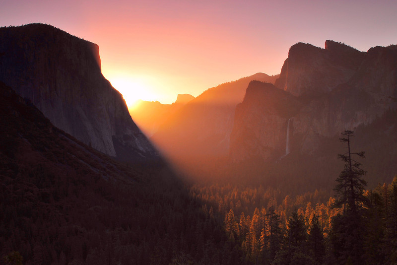 The sun rises over Yosemite Valley and is captured seconds before it peaks from behind El Capitan.  Half Dome is widely recognizable and sits on the illuminated horizon.  There may be no finer place to greet a new day than this iconic National Park.