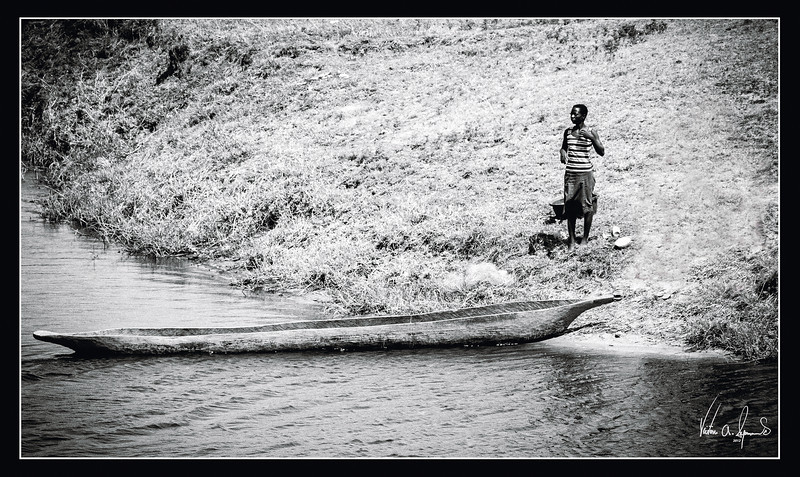 """NATIVE AND MOKORO CANOE"" - NATIVE WITH A MOKORO DUGOUT CANOE THAT WAS FISHING IN THE CHOBE NATIONAL PARK IN BOTSWANA, AFRICA"