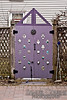 A purple garden gate with ornaments.