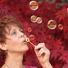 Redheaded woman blowing bubbles outside