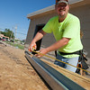 Robert Poindexter, with F&L Construction, measuring and cutting lumber at the future site of Bleu Garten at NW 10th and Hudson.