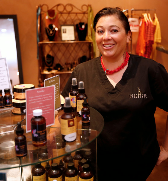 Holly Kirk , director of spa services at the Canebreak pauses for a photo with the lineup of products she developed.
