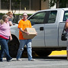 Employees of the Workers Compensation Commission carry boxes in the parking lot of the Denver Davidson Building Wednesday afternoon. Sixteen employees of the commission lost their jobs, after commission officials announced layoffs at the agency.  Photo by Brent Fuchs