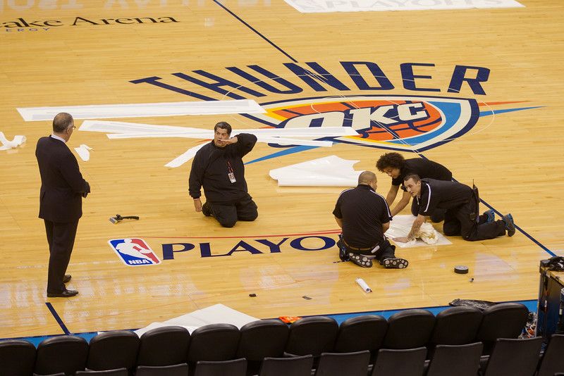 The NBA Playoff logo being placed on the floor of the Oklahoma CIty Thunder court.