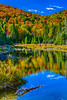 Brilliant fall foliage color in the mountains and a small pond in Mont-Tremblant National Park, Quebec, Canada.