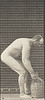 Nude man stooping and lifting a full demijohn to shoulder