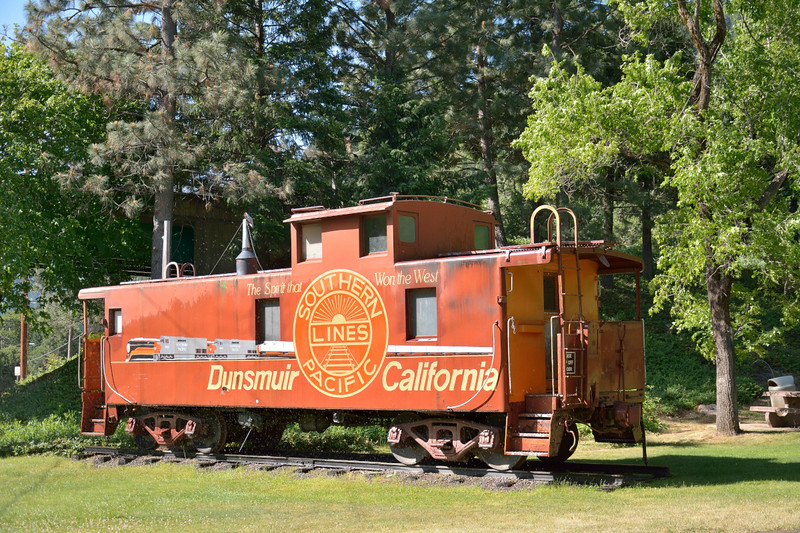 Northern Pacific steel, cupola cabose 10068, ex-Burlington Northern 11411, finds a use as an advertising hording City Park, Dunsmuir CA. <br /> <br /> 29 May 2014