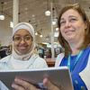 EPL Library Assistant, Lisa Snyder, shows EPL Student Page,  Rawda Baharun, an iPad.<br /> <br /> Taken on July 4, 2014 by James Cadden.
