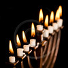 Beautiful lit hanukkah menorah on black.