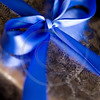 Blue Ribbon Tied in a Bow on Silver Gift.
