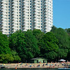 Many people sunbathing under huge tower block