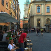 Crowds in a plaza in Gamla Stan, cathedral beyond