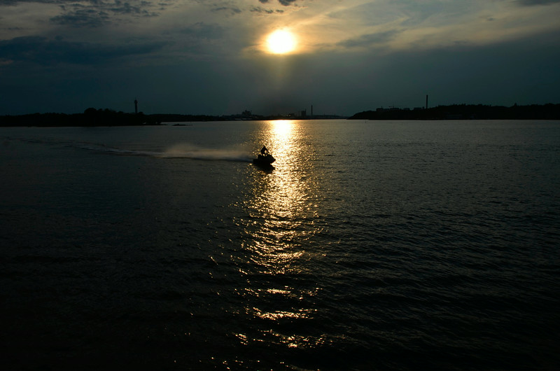 Approaching the harbor, a jet-ski crossed the path of the setting sun