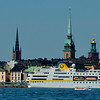 A cruise boat of reasonable size, colorful old apartment blocks and lots of spires