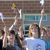Ben Cameron, left, and Chad Britton, eighth graders at Aspen Creek K-8 school, raise pinwheels in the air for the Pinwheels for Peace project on Wednesday at the school. Students from all grades planted pinwheels in the shape of peace signs. September 21, 2011 staff photo/ David R. Jennings