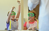 A youngster holds up a piece of litmus paper while learning about acids and bases from instructor Bill Vosburgh during the Science in the Summer program at the Indian Valley Library.   Thursday,  July 17, 2014.   Photo by Geoff Patton