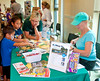 Linda Wagner (in dark green shirt) of the Conservancy of Southwest Florida shares craft activities with two young visitors