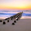 Remnants of an old pier extends out into the Atlantic Ocean surf and glowing daybreak sky, in Nags Head, the Outer Banks, North Carolina