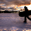 Owen Lheron, 12 is silhouetted against the setting sun and dark clouds as he heads home after a day of sledding on the campus of Brooks School in North Andover.<br /> Photo by Carl Russo