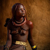 A beautiful Himba girl sitting outside her mud hut in Otjikandero Village, Damara Land, Namibia.  Africa.
