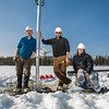 Associate Professor Mat Wooller, blue shirt, and Ph.D. candidate Jim Shobe, center, test a new vibra-coring system through a hole in lake ice to sample long cores of sediment deep below the lake's bottom. Also helping is Terry Smith, right, a North Pole High School student intern.