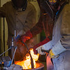 Art major Joel Isaak, left, returns a pot of molten bronze into the furnace as part of the process of creating a life-sized sculpture for his senior thesis in the UAF Fine Arts complex.