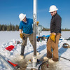 Associate Professor Mat Wooller, left, and Ph.D. candidate Jim Shobe test a new vibra-coring system through a hole in lake ice to sample long cores of sediment deep below the lake's bottom.