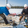 Associate Professor Mat Wooller, blue shirt, and Ph.D. candidate Jim Shobe, right, test a new vibra-coring system through a hole in lake ice to sample long cores of sediment deep below the lake's bottom.