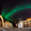 The aurora borealis dances across the night sky above the annual ice arch on UAF's campus.