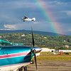 A rainbow appears behind a small plane as it takes off from the Fairibanks International Airport on a summer morning.