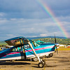 A rainbow appears behind a small plane as it awaits takeoff from the Fairibanks International Airport on a summer morning.