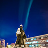 A strand of light from the aurora borealis floats above the statue of Charles Bunnell and the Bunnell Building on the Fairbanks campus.
