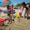 RYAN HUTTON/ Staff photo.<br /> Brooklyn Lake, 2, goes to spray her sister Fiona, 6, with water while she builds a sandcastle with Ava Maeve Doane, 8, at Singing Beach in Manchester on Wednesday.
