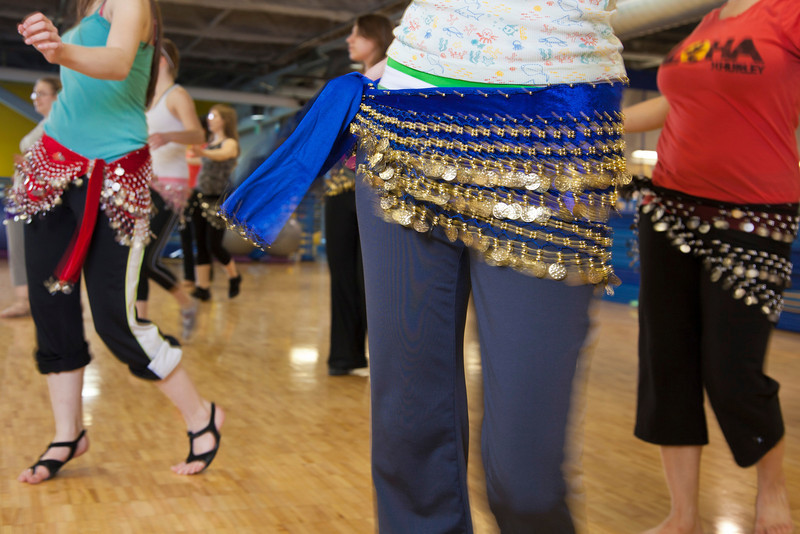 The students of the middle eastern dance class learn how to shimmy in their beaded skirts.