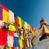Prayer flags flutter in the breeze strung from the top of Boudhas' stupa. Nepal