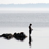 Waiting - This young boy got an early start on his fishing one summer morning. I watched him for awhile as he patiently waited for his catch. He seemed to enjoy the peacefulness of the morning.