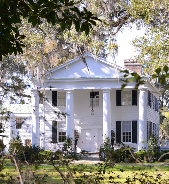Annandale Plantation<br /> <br /> Annandale Plantation, originally named Millbrook, the site of the first tide-operated rice mill constructed in the state (ca. 1792), is one of South Carolina's finest remaining examples of the rice-plantation era. During the 1850s, Annandale was among the most prosperous of the rice plantations, working approximately 230 slaves and producing 900,000 pounds of rice. Andrew Johnston's father bequeathed the property to him, and he built the present plantation house in 1833. At that time he renamed the property Annandale after the birthplace of his ancestors in Annandale, Scotland. This two story Greek Revival structure, c.1833, is an excellent example of its style and period, and the giant-order quasi-Tuscan portico sets it off splendidly. The vent in the pediment is a later addition. A rear addition was skillfully integrated into the existing structure ca. 1880; an additional wing to the north was constructed in 1966. All interior moulding details in the front of the house are original. They include the paneled doors, window frames and sills, and beaded baseboards. Window and door frame treatments use square corner blocks, into which are carved acanthus leaves. Situated in a grove of live oaks and landscaped gardens, Annandale includes two existing outbuildings: a slave cabin which has been converted into a recreation building and the plantation-doctor's house, now a residence. Listed in the National Register October 25, 1973.