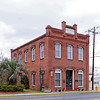 """Bank of Hampton<br /> <br /> In 1891, several prominent citizens of the town of Hampton organized the Bank of Hampton. Purchasing a lot across from the County Courthouse, they engaged architect/builder Vincent J. Fontaine to construct a prominent edifice for the new bank. Fontaine, a French immigrant, studied architecture in Italy before moving to South Carolina in the early 1870s. The two-story Italianate influenced brick building was completed in 1892. The building features segmental arches over door and window openings, and low flat parapets at the side elevations. As the county seat, Hampton had six lawyers by 1883, several of which rented upstairs offices. Establishment of the bank was an important factor in securing the town's position as a regional center, and by 1905 Hampton was listed as a """"banking town"""" in a statewide business directory. The Bank of Hampton operated successfully until 1926, and three years later the building was purchased from its receivers by their competitors, The Loan and Exchange Bank. From the 1930s to the 1960s the building was operated as rental commercial space, still maintaining the upstairs law offices. In 1987, heirs of the buildings' owners gave it to the town of Hampton. The building since then houses the Hampton Museum and Visitors' Center. Listed in the National Register May 30, 2001."""