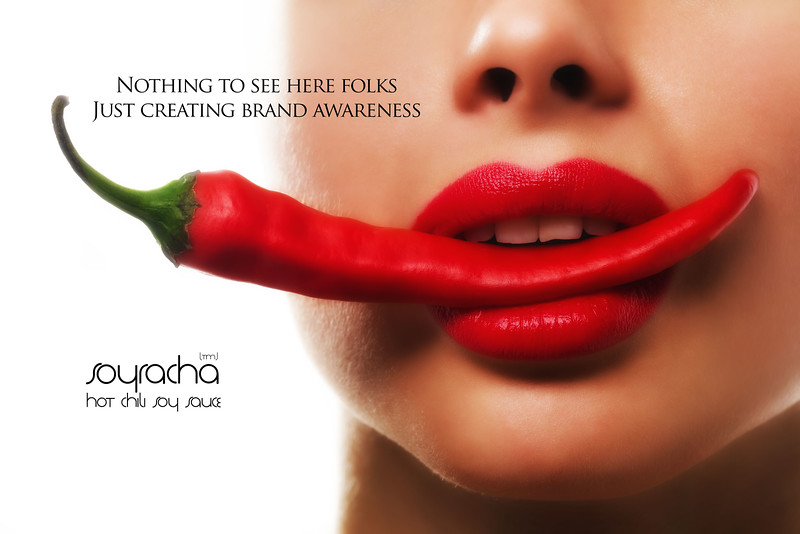 Female mouth holding red hot chili pepper. She has bright red lipstick on her lips.