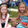 From left, Olivia, dog Summer, and Alexa Unger sat together along Queen Street waiting for the start of the 2012 Newtown Labor Day Parade. (Hallabeck photo)