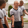 4th Company candidates speaking to each-other in between obstacle course attempts during obstacle course training at SUNY Maritime College on July 16th, 2014. The candidates are laughing as they point out their humorously similar minor injuries.