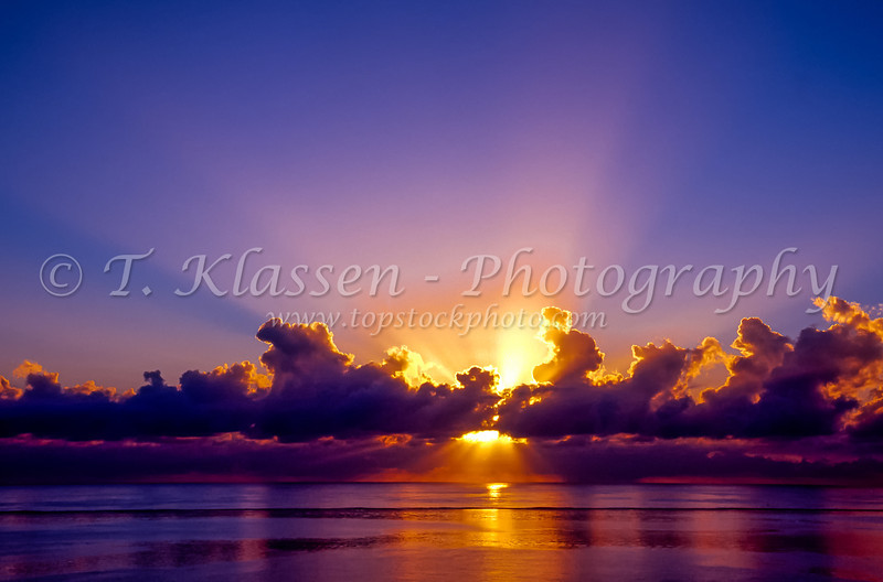 A dramatic sunburst sunset over the Caribbean Sea in the West Indies.
